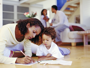 African american mother and son drawing on floorの写真素材 [FYI02128769]