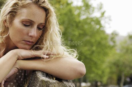 Woman looking down outdoorsの写真素材 [FYI02128774]