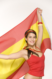 Young woman holding Spanish flagの写真素材 [FYI02128775]