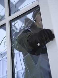 Burglar reaching through broken glass on doorの写真素材 [FYI02128813]