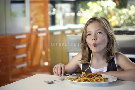 Girl eating pasta at tableの写真素材 [FYI02128814]