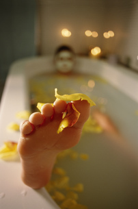 Close-up of foot of person relaxing in bathの写真素材 [FYI02128834]