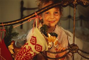 Young girl looks through iron railing anticipation Christmas morningの写真素材 [FYI02128852]
