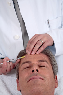 Man receiving anti-aging injection in faceの写真素材 [FYI02128883]