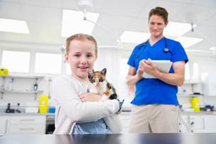 Vet with pet kitten cat at table in surgery with child owner smiling at cameraの写真素材 [FYI02128893]