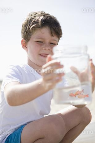 Boy looking at jar on beachの写真素材 [FYI02128912]
