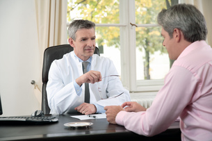 Male doctor talking to patient in officeの写真素材 [FYI02128953]