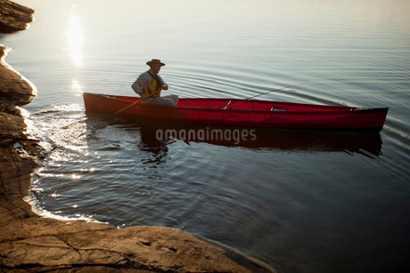 Mid adult man rowing boat in lakeの写真素材 [FYI02128988]