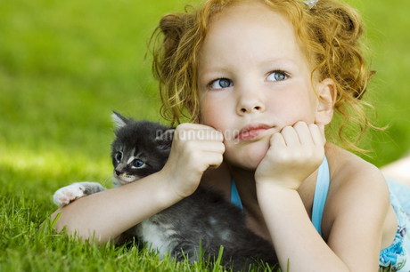 Young girl with kitten in grassの写真素材 [FYI02129030]
