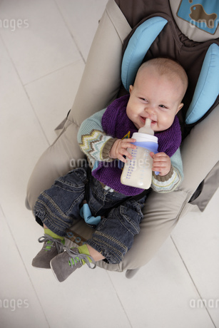 Baby with bottle in car seatの写真素材 [FYI02129052]