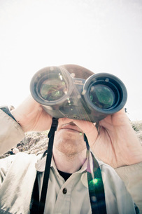 Mid adult man looking through binocularsの写真素材 [FYI02129055]