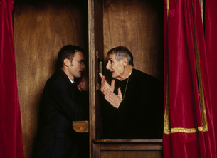 Businessman in confessional with priestの写真素材 [FYI02129094]