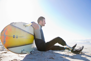 Surfer With Artificial Leg Sitting On Beachの写真素材 [FYI02129112]