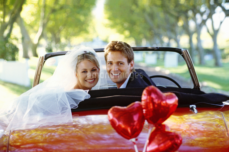 Bride and groom in red convertible, heart shaped balloons tied to bumperの写真素材 [FYI02129119]