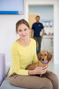 Pet dog owner in vet surgery waiting room reception smiling at cameraの写真素材 [FYI02129133]