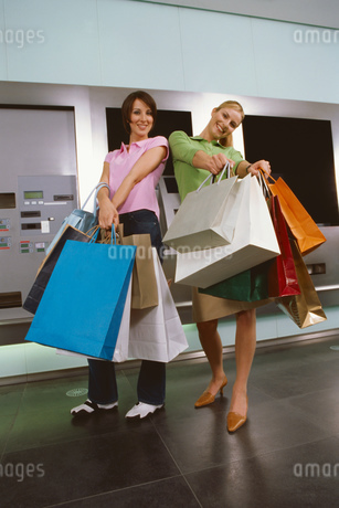 Two young women holding out shopping bagsの写真素材 [FYI02129155]