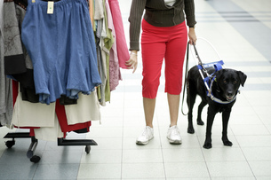 Blind woman and seeing eye dog shopping for clothingの写真素材 [FYI02129207]