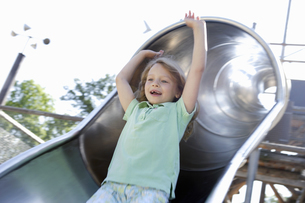 Girl sliding down slide at playgroundの写真素材 [FYI02129222]
