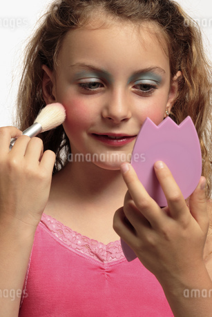 Young girl putting on makeupの写真素材 [FYI02129229]