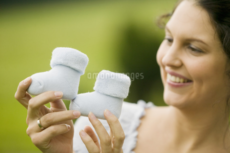 Woman holding up two baby bootsの写真素材 [FYI02129254]