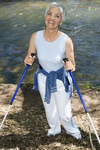 Senior woman with walking sticks on nature trailの写真素材 [FYI02129279]