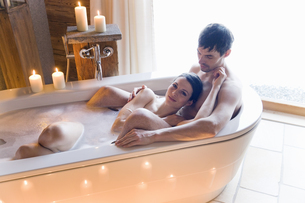 Couple enjoying bath together in candle lightの写真素材 [FYI02129288]