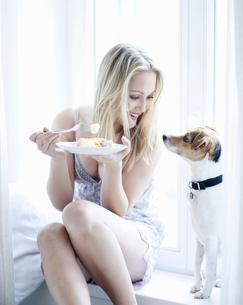 Teenage girl eating with pet dogの写真素材 [FYI02129305]