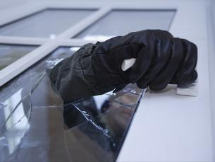 Burglar reaching through broken glass on doorの写真素材 [FYI02129316]