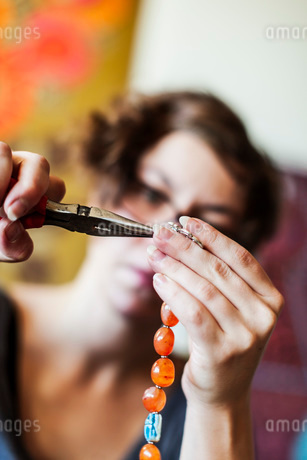Mid adult woman using pliers to make bead jewelry, DIYの写真素材 [FYI02129357]