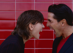 Couple yelling at each other at close range, red tile wall in backgroundの写真素材 [FYI02129384]