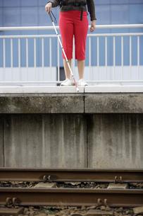 Blind woman at edge of train station platformの写真素材 [FYI02129401]