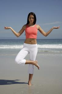 Woman practicing yoga at beachの写真素材 [FYI02129461]