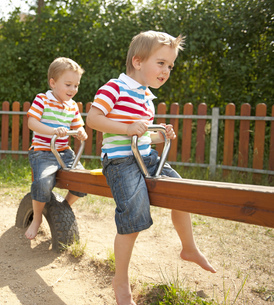 Twin brothers playing on seesaw in playgroundの写真素材 [FYI02129482]