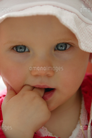 View of a baby girl with fingers in mouthの写真素材 [FYI02129592]