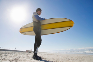 Surfer With Artificial Leg Standing On Beachの写真素材 [FYI02129616]