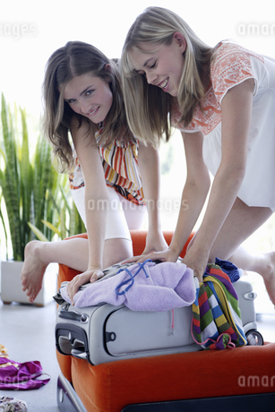 Teenage girls packing for vacationの写真素材 [FYI02129617]