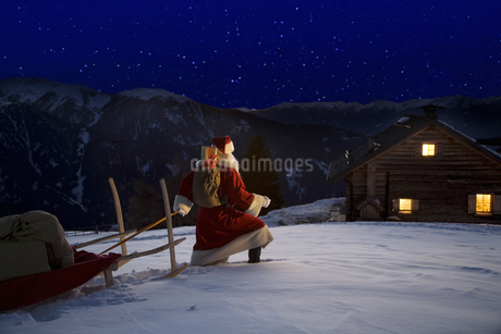 Santa Claus pulling sleigh towards chalet, Luesener Alm, Dolomite Alps, South Tyrol, Italyの写真素材 [FYI02129632]