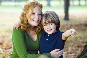 Mother and boy in autumn forestの写真素材 [FYI02129676]