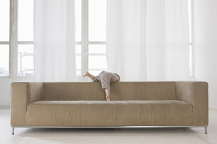 A little boy climbing over the back of a sofaの写真素材 [FYI02129800]