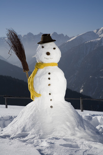 Snowman with scarf and broom, Luesener Alm, Dolomite Alps, South Tyrol, Italyの写真素材 [FYI02129911]