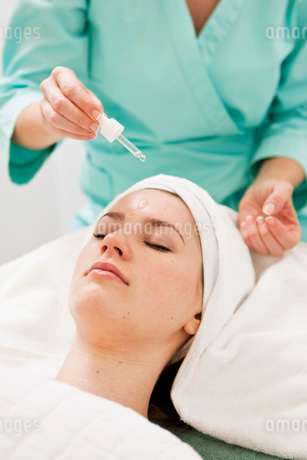 Massage therapist applying oil from pipette on young woman'の写真素材 [FYI02129946]