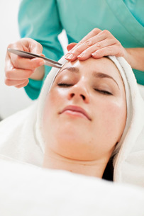 Young woman having eyebrows plucked from tweezers at beautyの写真素材 [FYI02129968]