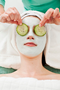 Massage therapistkeeping slices of cucumber on young womanの写真素材 [FYI02129974]
