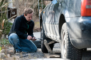 Mid adult man changing car's tire on roadの写真素材 [FYI02129992]