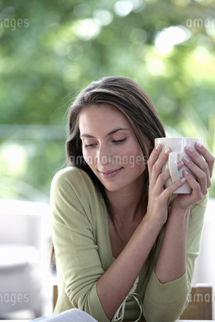 Portrait of a young woman holding a cup of coffeeの写真素材 [FYI02130030]