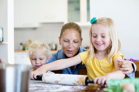 Happy woman looking at little daughter rolling dough on tablの写真素材 [FYI02130048]