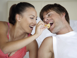 Woman feeding boyfriend in bedの写真素材 [FYI02130058]