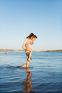 Young man giving woman a piggy back ride in water at beachの写真素材 [FYI02130066]