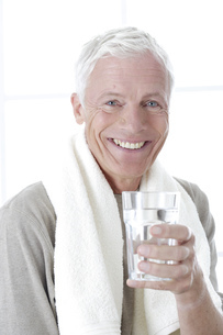 Close up of senior man smiling with glass of water and towel around neckの写真素材 [FYI02130068]