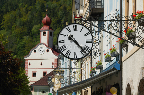 View of a clock hanging from a sign post outside a building, Gmuend, Kaernten, Austriaの写真素材 [FYI02130097]